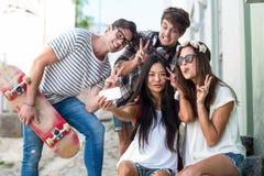 Amis de hanche prenant le selfie se reposant sur des étapes Images libres de droits