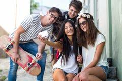 Amis de hanche prenant le selfie se reposant sur des étapes Photo libre de droits
