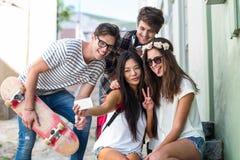 Amis de hanche prenant le selfie se reposant sur des étapes Photographie stock