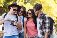 amis de hanche regardant l'appareil photo numérique Photo libre de droits