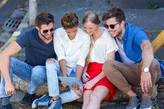 Amis de hanche regardant le comprimé et s'asseyant sur le trottoir Photo stock
