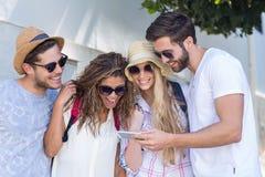 Amis de hanche regardant le smartphone Photographie stock libre de droits