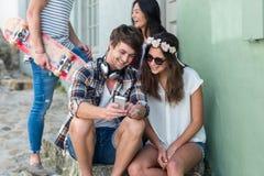 Amis de hanche regardant le smartphone et s'asseyant sur des étapes Images stock