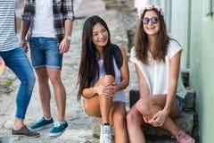 Amis de hanche s'asseyant sur des étapes dans la ville Photographie stock