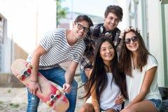 Amis de hanche s'asseyant sur des étapes et souriant à l'appareil-photo Photographie stock