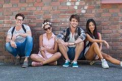 Amis de hanche s'asseyant sur le plancher Image libre de droits