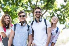 Amis de hanche souriant à l'appareil-photo Photographie stock libre de droits