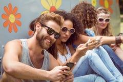 Amis de hippie à l'aide de leurs téléphones Images libres de droits