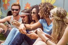 Amis de hippie à l'aide de leurs téléphones Images stock