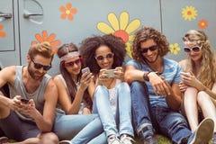 Amis de hippie à l'aide de leurs téléphones Photo stock
