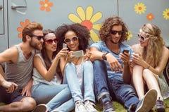 Amis de hippie à l'aide de leurs téléphones Photographie stock libre de droits