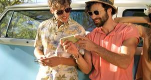 Amis de hippie regardant le smartphone et rire clips vidéos