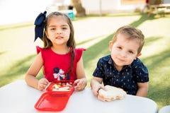 Amis de jardin d'enfants mangeant le déjeuner ensemble Photographie stock
