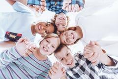 Amis de jardin d'enfants tenant des mains Images stock