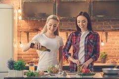 Amis de jeunes femmes faisant cuire le repas ensemble à la maison Photos stock