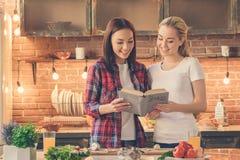 Amis de jeunes femmes faisant cuire le repas ensemble à la maison Photo libre de droits