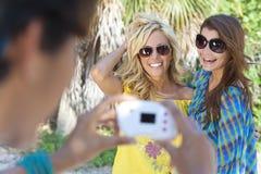 Amis de jeunes femmes prenant des photos des vacances Images stock