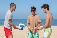 Amis de l'équipe trois jouant le football au bord de la mer Image libre de droits