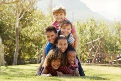 Amis de la préadolescence d'école se trouvant une pile en parc Images libres de droits