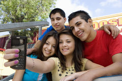Amis de lycée prenant l'autoportrait avec le téléphone portable Images stock