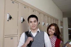 Amis de lycée se tenant près des casiers d'école Photos libres de droits