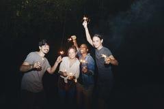 Amis de métis jouant avec la célébration de cierges magiques et le concept de fête de partie Photographie stock