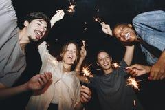 Amis de métis jouant avec la célébration de cierges magiques et le concept de fête de partie Images libres de droits