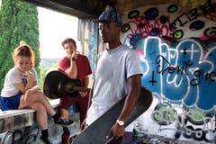 Amis de musicien ayant l'amusement dans un endroit urbain Photos stock