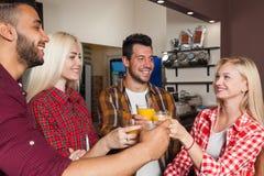 Amis de personnes buvant du jus d'orange, grillant au compteur de barre, à l'homme de course de mélange et aux acclamations de fe Photographie stock