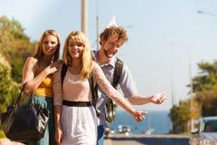 Amis de personnes faisant de l'auto-stop des vacances d'été Photos stock