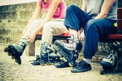 Amis de personnes mettant sur des patins de rouleau extérieurs Images stock
