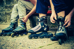 Amis de personnes mettant sur des patins de rouleau extérieurs Photos libres de droits