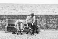 Amis de personnes mettant sur des patins de rouleau extérieurs Image stock