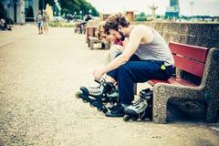 Amis de personnes mettant sur des patins de rouleau extérieurs Photos stock