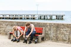 Amis de personnes mettant sur des patins de rouleau extérieurs Photographie stock libre de droits