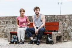 Amis de personnes mettant sur des patins de rouleau extérieurs Photo stock