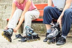 Amis de personnes mettant sur des patins de rouleau extérieurs Photographie stock