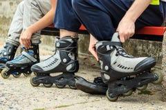 Amis de personnes mettant sur des patins de rouleau extérieurs Photo libre de droits