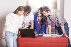 Amis de personnes travaillant à la maison à la table Images stock