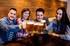 Amis de portrait grillant la bière au restaurant Photographie stock