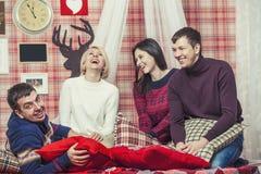 Amis de quatre hommes et femmes riant et parlant dans le bedroo Images stock