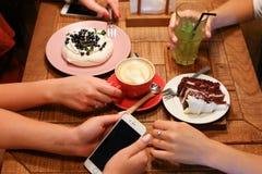 Amis de réunion en cafés et tarte aux cerises de confiserie d'ordre, mer Photos stock