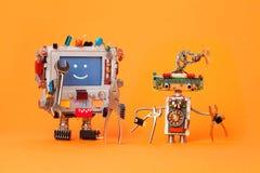 Amis de robots prêts pour la réparation de service Les caractères robotiques drôles avec l'instrument, pinces remettent des clés  Photographie stock