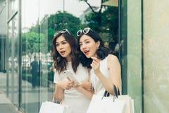 Amis de Shopaholic avec des paniers marchant sur la rue au m Photographie stock libre de droits