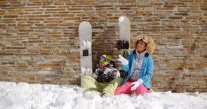 Amis de snowboarding s'asseyant dans la pile de la neige Images stock