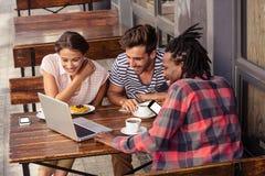 Amis de sourire à l'aide d'un ordinateur portable Image libre de droits
