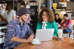 Amis de sourire à l'aide de l'ordinateur portable dans le restaurant Photo libre de droits