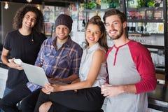 Amis de sourire à l'aide de l'ordinateur portable dans le restaurant Photographie stock