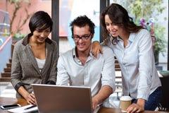 Amis de sourire à l'aide de l'ordinateur portable ensemble Image stock