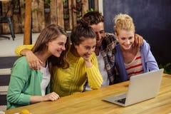 Amis de sourire à l'aide de l'ordinateur portable ensemble Images stock